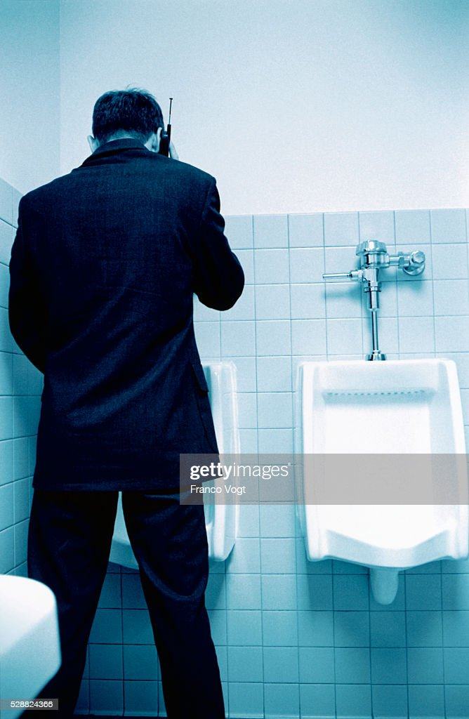 Man Talking On Cell Phone While Using Urinal Stock Photo