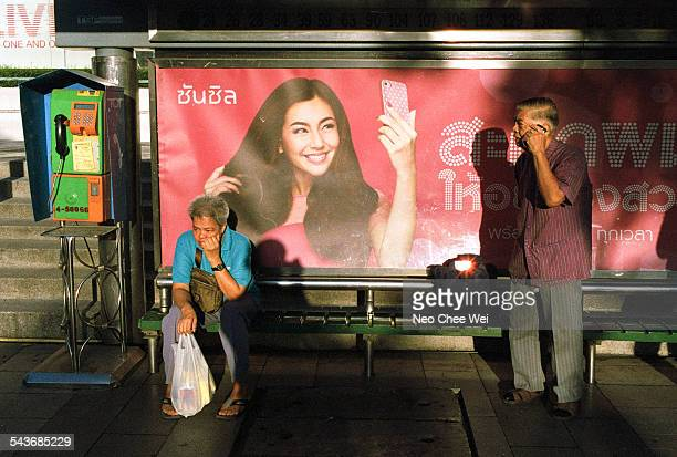 Man talking on his cellphone standing next to a billboard with a woman taking a selfie with her cellphone at a bus stop in Bangkok Thailand