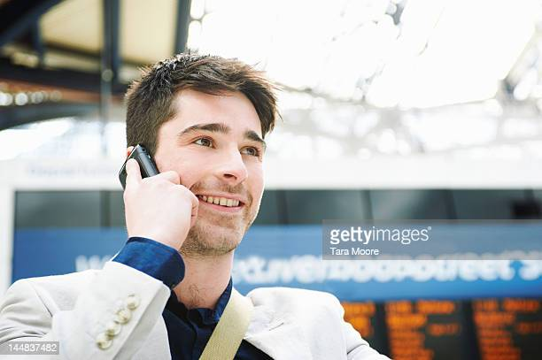 man talking on mobile and smiling at train station - newtechnology stock pictures, royalty-free photos & images