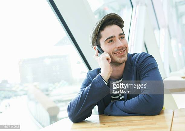 man talking on mobile in cafe - flat cap stock pictures, royalty-free photos & images