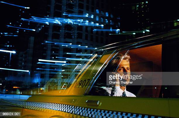 Man talking on mobile phone in back of taxi, USA (blurred motion)
