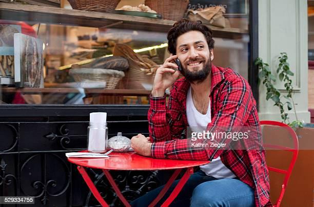 man talking on mobile phone in café