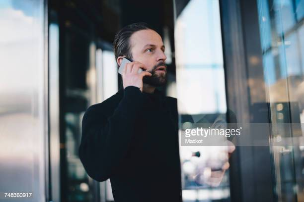 Man talking on mobile phone while standing by display cabinet at store