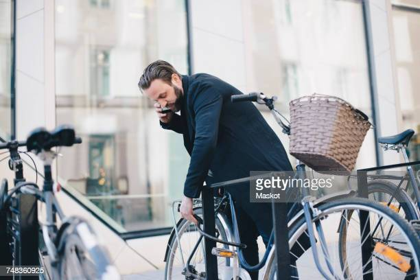 Man talking on mobile phone while unlocking bicycle in city