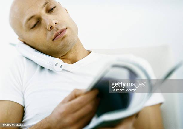 Man talking on phone and looking through magazine