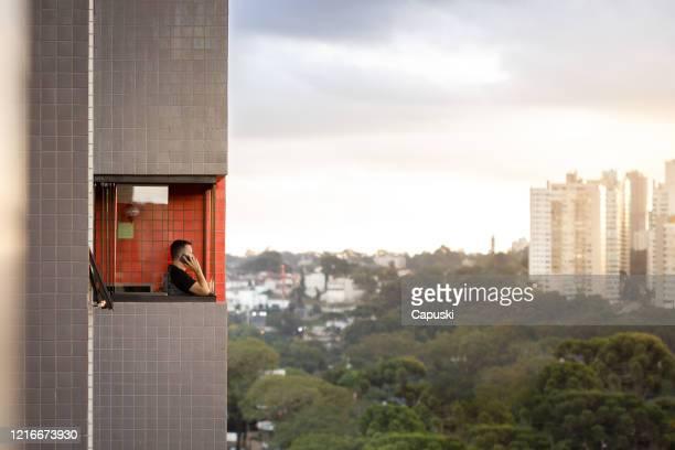 homem falando ao telefone na varanda de casa - sacada - fotografias e filmes do acervo