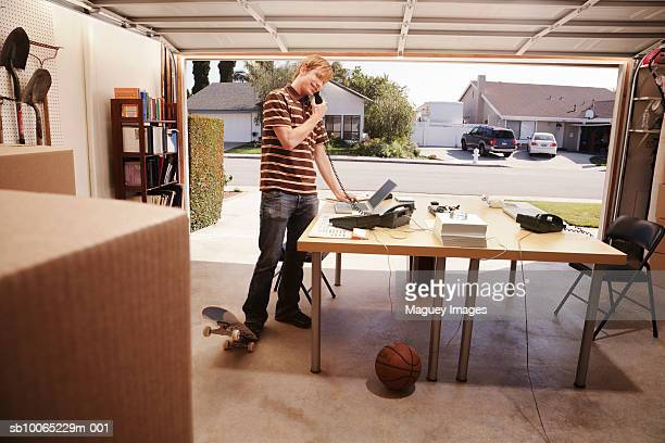 man talking on phone in office space in garage - costa mesa stock photos and pictures