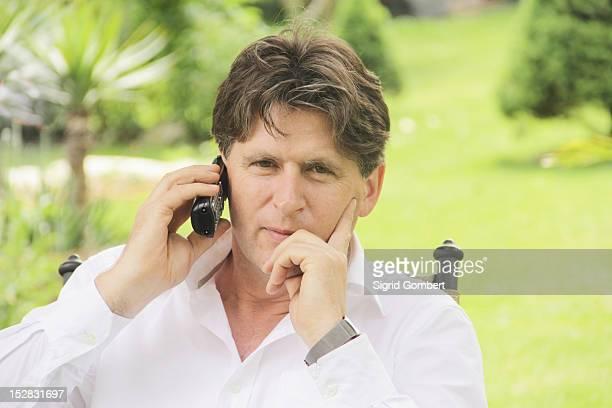man talking on phone outdoors - sigrid gombert fotografías e imágenes de stock