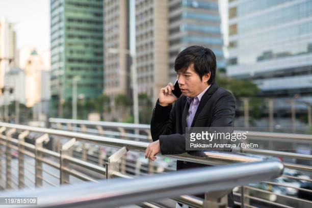 man talking on phone while standing by railing outdoors - abbigliamento da lavoro formale foto e immagini stock