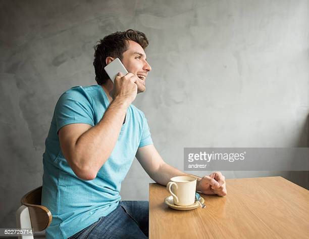 Man talking on the phone at a cafe