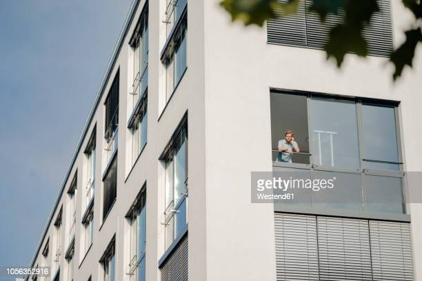 man talking on the phone, looking out of office window - looking at view - fotografias e filmes do acervo