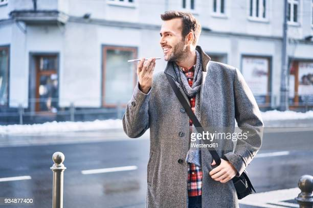 Man talking on the phone on city street during sunny winter day