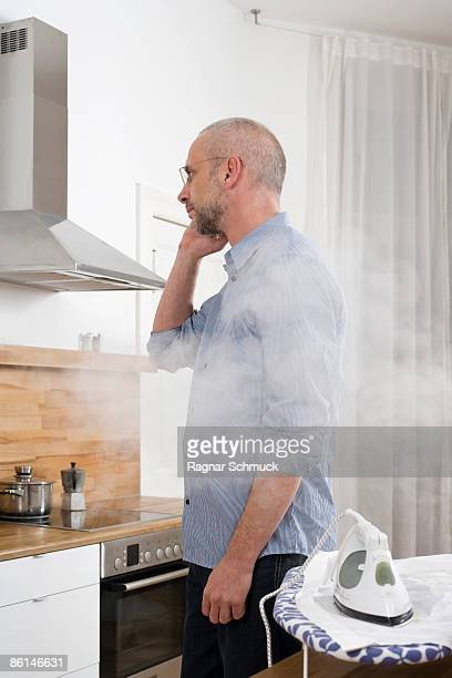 A man talking on the phone with his back to an iron which is burning his shirt