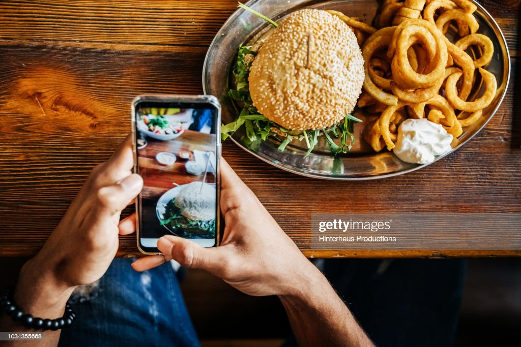 Man Talking Picture Of Burger With Smartphone : Stock Photo