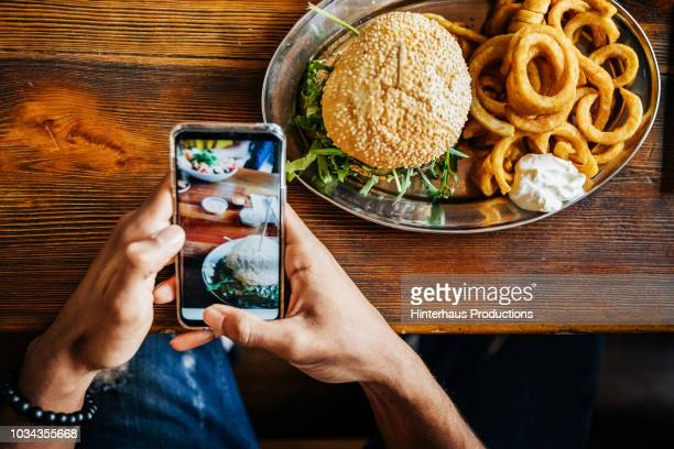 man talking picture of burger with smartphone - photographing stock pictures, royalty-free photos & images