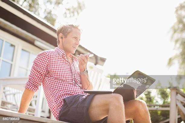 Man talking through hands-free device on porch against clear sky