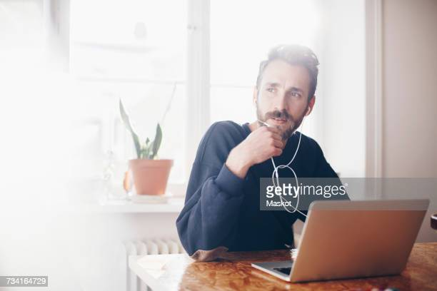 Man talking through headphones by laptop against window at home