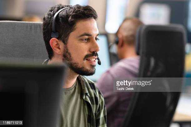 man talking to a customer over a headset - real estate agent stock pictures, royalty-free photos & images