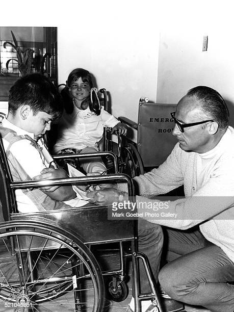 Man talking to boy in wheelchair late 1960s