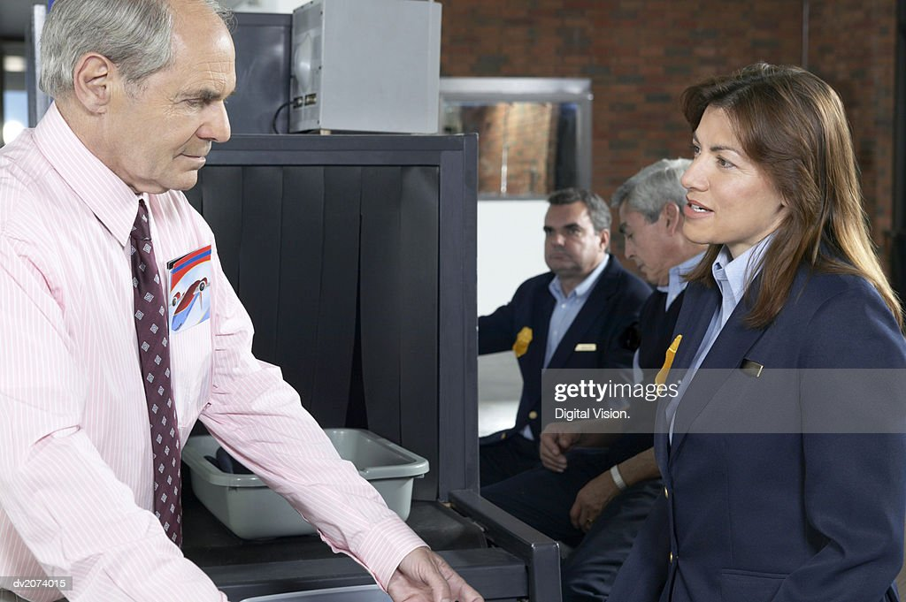 Man Talking to Customs Officers in an Airport : Stock Photo