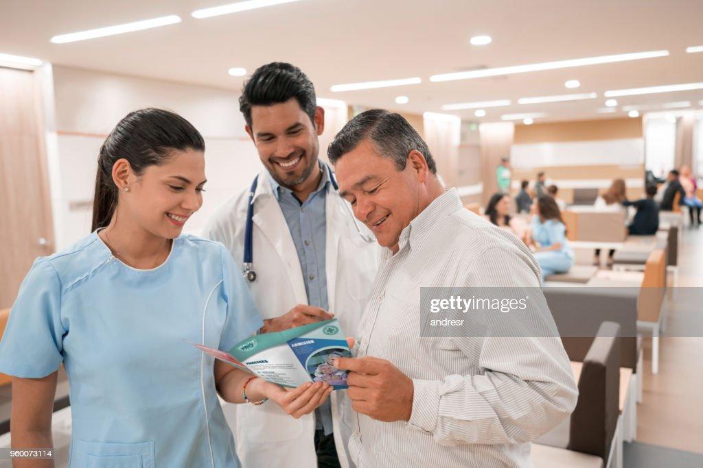 Mann im Gespräch mit Arzt und Krankenschwester beim Betrachten einer Broschüre ein Altersheim für seine Eltern : Stock-Foto