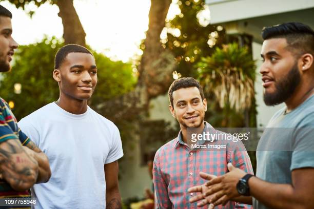 man talking to friends in party - modern manhood stock pictures, royalty-free photos & images