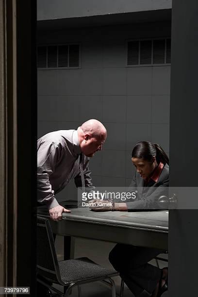 Man talking to handcuffed woman in interrogation room, seen through doorway
