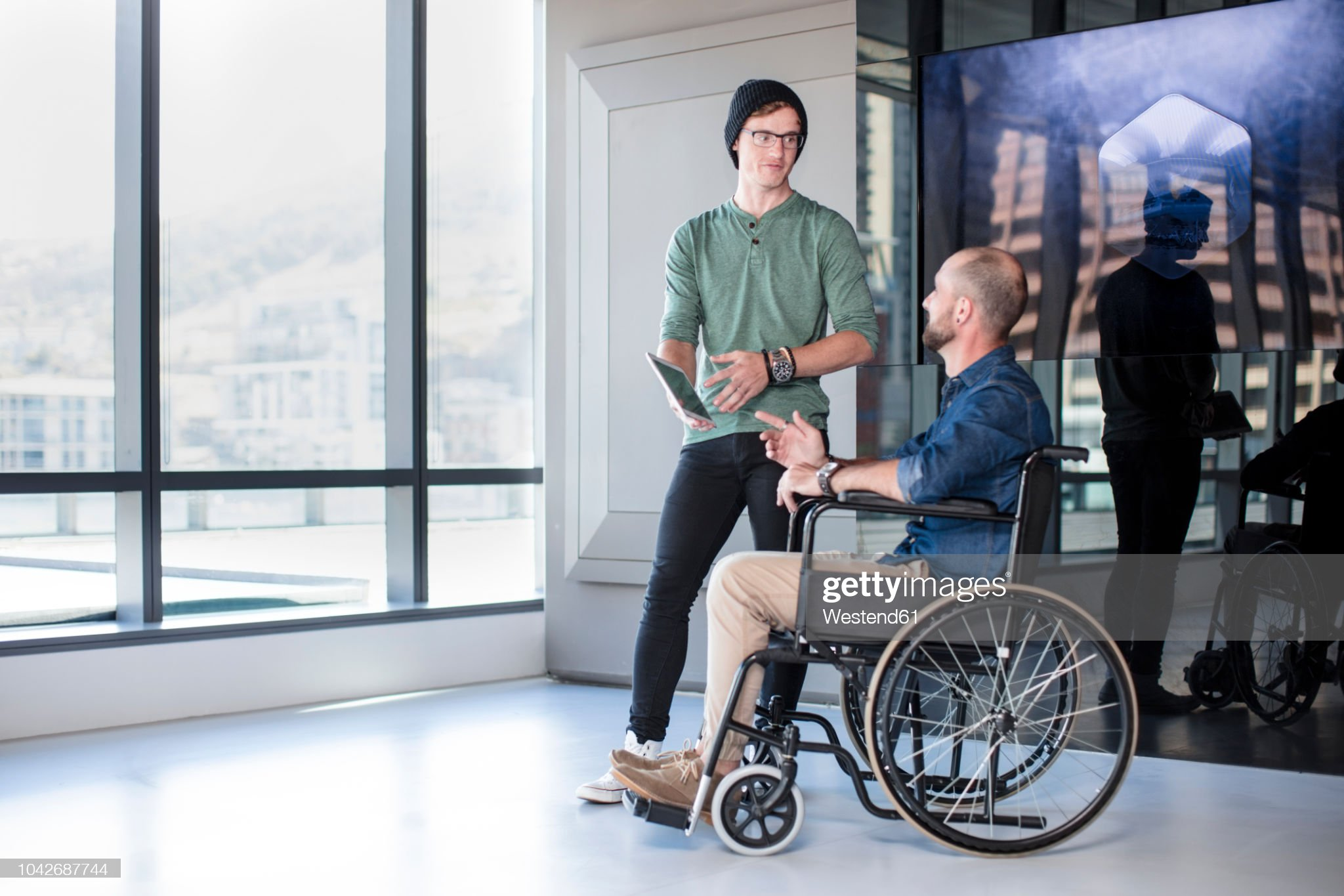 Man talking to handicapped colleague in wheelchair : Photo