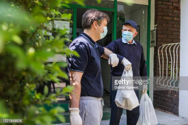 man talking to his senior neighbor holding bags of groceries, both wearing protective gear during pandemic - neighbour stock pictures, royalty-free photos & images