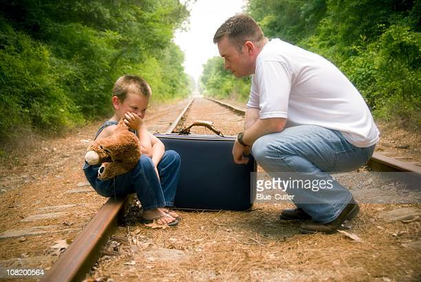 Man Talking to Little Boy Sitting on Tracks with Suitcase