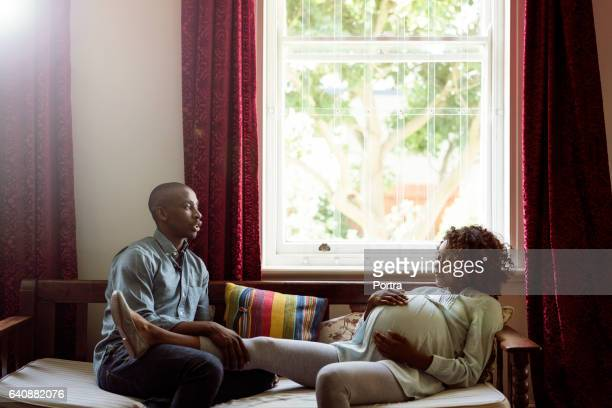 Man talking to pregnant woman at brightly lit home