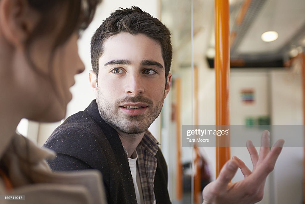 man talking to woman in train : ストックフォト
