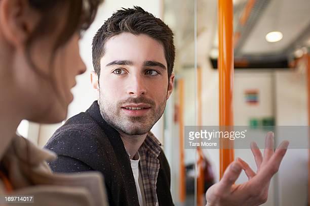man talking to woman in train