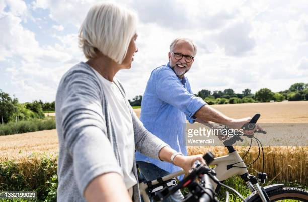 man talking to woman while walking with bicycle on sunny day - 55 59 anni foto e immagini stock
