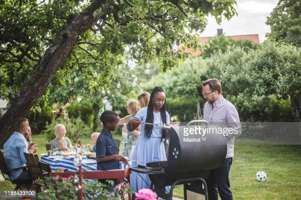 man talking to woman with son preparing food at barbecue grill against friends  during weekend party - garden party stock pictures, royalty-free photos & images