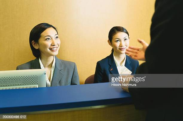 Man talking to women at reception desk