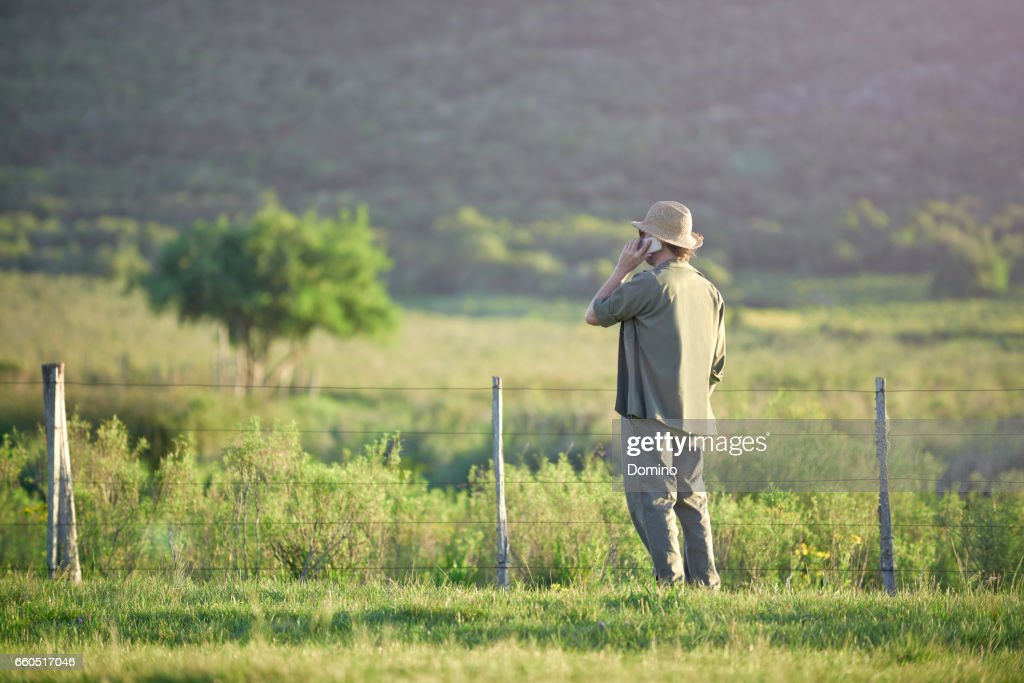 Man talking with smartphone in landscape : Stock Photo