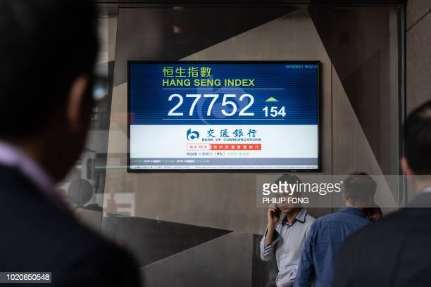 A man talks in his mobile phone underneath a stocks display showing the Hang Seng Index at 27752 after the close of trading in Hong Kong on August 21...