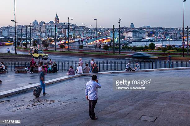 A man talks into a mobile next to the Golden Horn as the sunset arrives on June 13 2014 in Istanbul Turkey