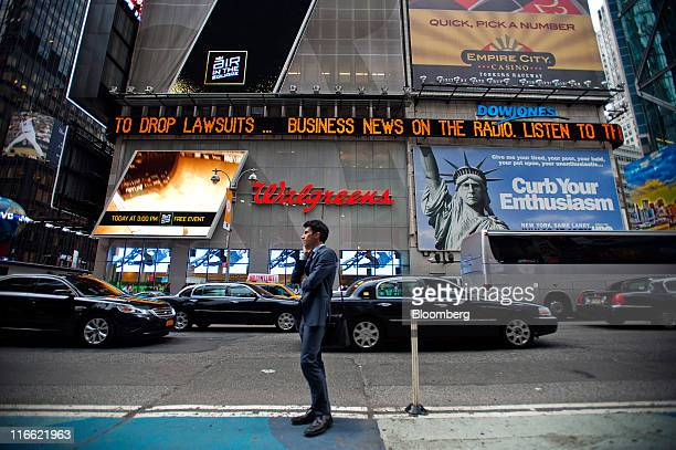 A man talks on a cell phone in front of the Dow Jones news ticker in Times Square in New York US on Thursday June 16 2011 The Bloomberg via Getty...
