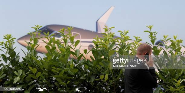 A man talks on a mobile phhone as he walks past the Embraer display booth at the Farnborough Airshow south west of London on July 19 2018