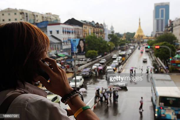 A man talks on a mobile phone as he looks towards the Sule Pagoda in downtown Yangon Myanmar on Tuesday June 4 2013 Myanmar's efforts to catch up...