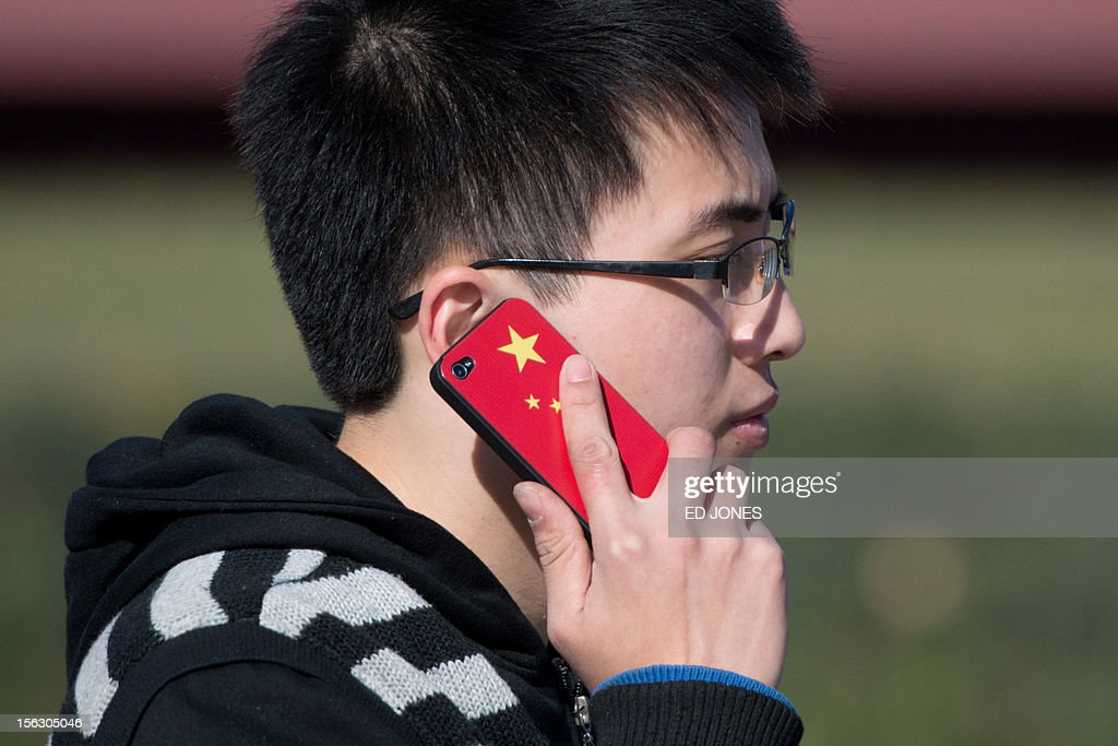 A man talks on a mobile phone featuring a Chinese flag near Tiananmen Square in Beijing on November 13, 2012. China's Communist Party will on November 15 unveil the new set of top leaders who will run the country for the next decade, one day after its week-long congress ends. AFP PHOTO / Ed Jones