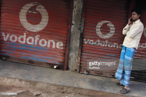 Man talks on a mobile phone outside the downed shutters of a shop painted with a logo of Vodafone in Mumbai, India on 15 January 2020.