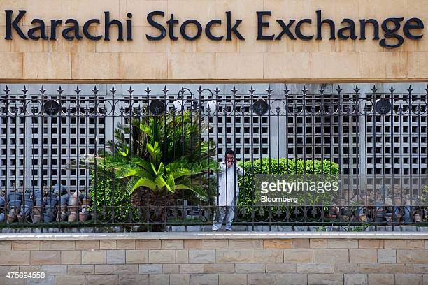 A man talks on a mobile phone outside the Karachi Stock Exchange KSE building in Karachi Pakistan on Thursday May 28 2015 Pakistan's budget is...
