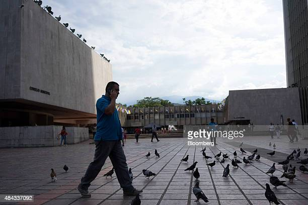 A man talks on a mobile phone while walking past townhall at the Plaza de la Alcaldia in Cali Colombia on Wednesday Aug 12 2015 Colombia's central...