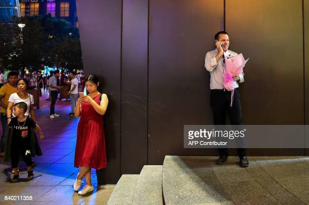 A man talks on a phone as he holds a bouquet of flowers during the Qixi Festival or Chinese Valentine's Day in Shanghai on August 28 2017 While...