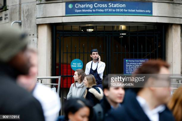 A man talks on a phone outside a closed and shuttered entrance to Charing Cross Station in central London on January 23 2018 after a gas leak closed...