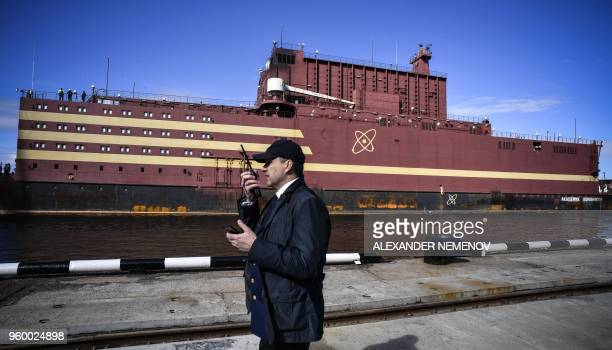 A man talks on an the radio as floating power unit Akademik Lomonosov is being towed to Atomflot moorage of the Russian northern port city of...