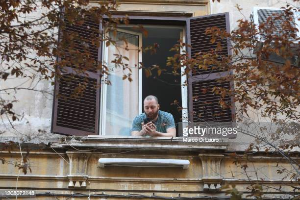A man talks on his cell phone at his home window on March 22 2020 in Rome Italy As Italy extends its nationwide lockdown to control the spread of...